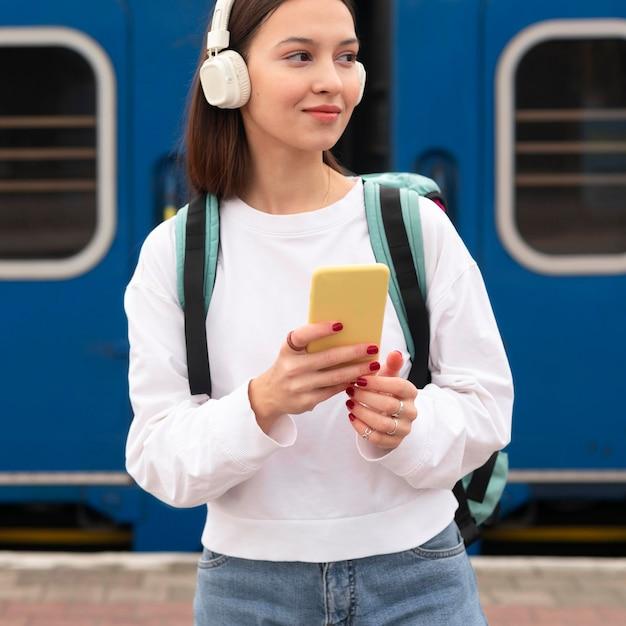 Ragazza carina alla stazione ferroviaria ascoltando musica Foto Gratuite