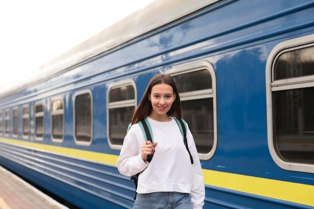 Ragazza carina presso la stazione ferroviaria sorride Foto Gratuite