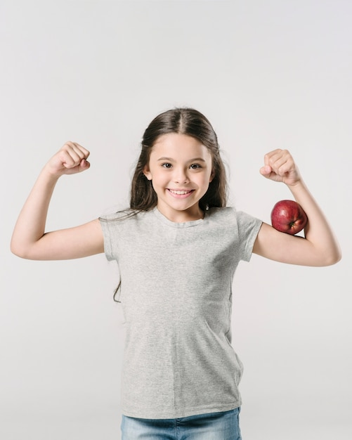 Cute girl standing with apple on bicep in studio Free Photo