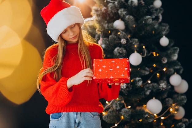 クリスマスツリーの赤いサンタ帽子のかわいい女の子のティーンエイジャー 無料写真