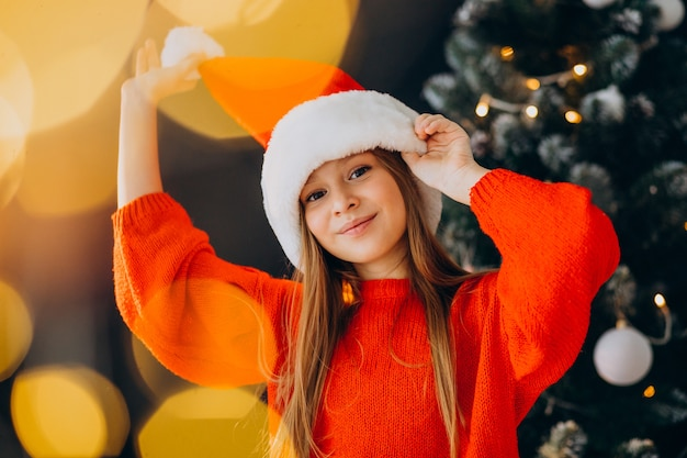 Cute girl teenager in red santa hat by christmas tree Free Photo