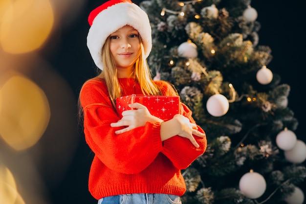 Adolescente sveglio della ragazza in cappello rosso della santa da albero di natale Foto Gratuite