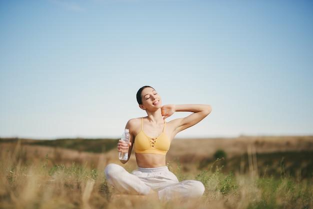Cute girl training on blue sky in a field Free Photo