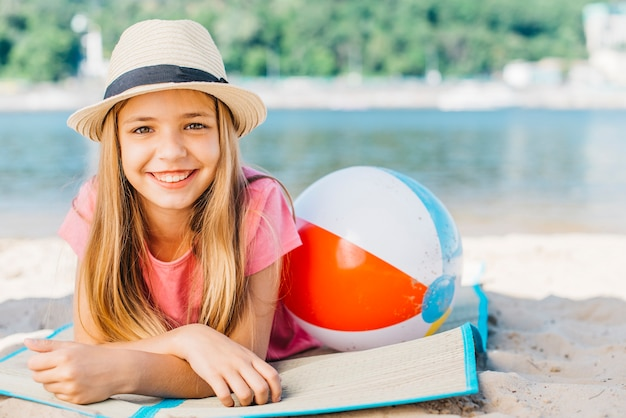 Cute girl with ball smiling on coast Free Photo
