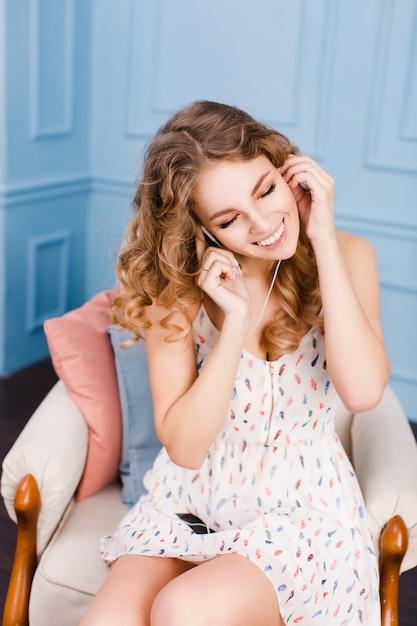 ブロンドの巻き毛のかわいい女の子は、青い壁と茶色の家具が付いているスタジオのアームチェアに座っています。 無料写真
