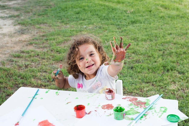 Cute girl with hands painted in colorful paints Free Photo