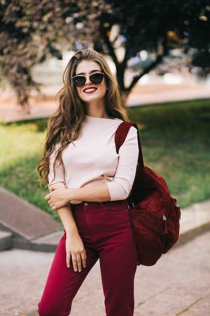 Ragazza carina con capelli lunghi in occhiali da sole con borsa vinosa e pantaloni sorride nel parco cittadino. Foto Gratuite