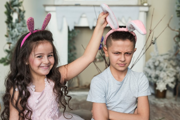 Cute girl with offended boy in bunny ears Free Photo
