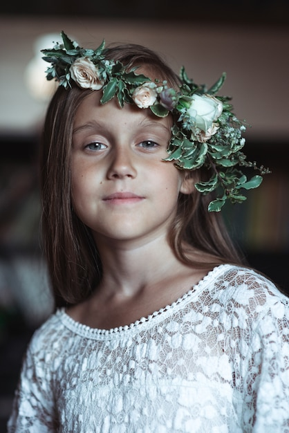 Cute girl with very long hair and a beautiful wreath of flowers on her head Premium Photo