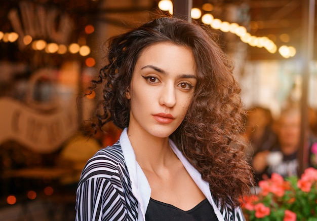 Cute girl with wavy hair, portrait of a girl in a cafe. Premium Photo