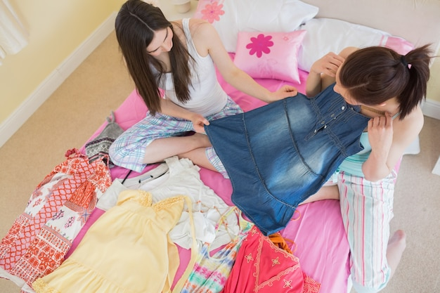 Cute girls looking at a denim dress at a sleepover Premium Photo