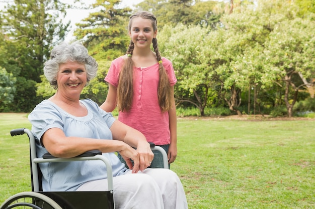 Cute granddaughter with grandmother in her wheelchair Premium Photo