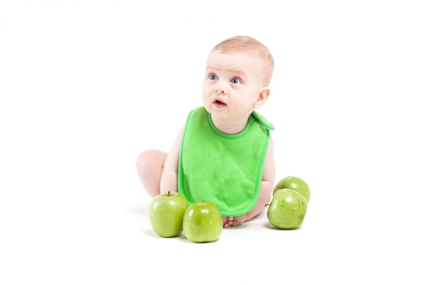 Cute happy little boy in green bib near green apples Premium Photo