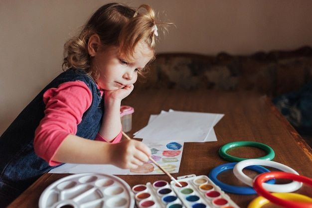 Cute happy little girl, adorable preschooler, painting with wate Free Photo
