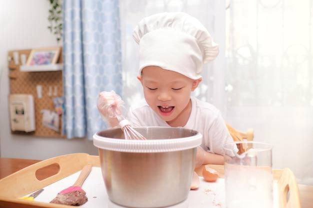 かわいい幸せな笑顔アジア4歳の男の子の子供が楽しんでケーキやパンケーキの準備を楽しんでいるプロセスミックス生地を自宅で泡立て器を使用して Premium写真