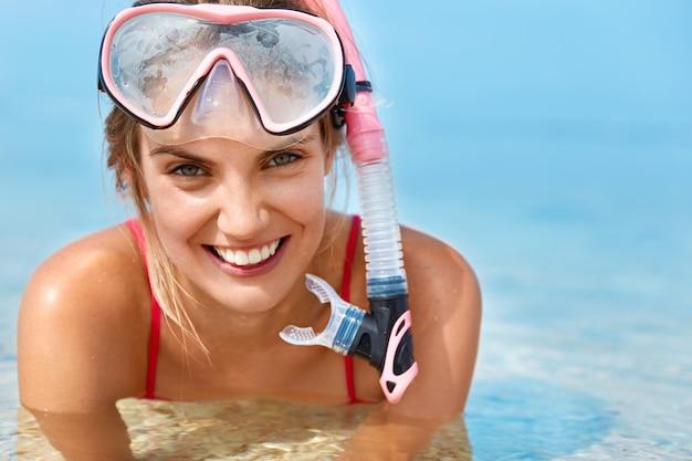 Милая счастливая женщина носит маску для подводного плавания, плавает в бассейне, позирует в чистой голубой воде, имеет позитивную улыбку, ведет активный образ жизни. спортивная женщина с маской и трубкой под водой. водные развлечения Бесплатные Фотографии