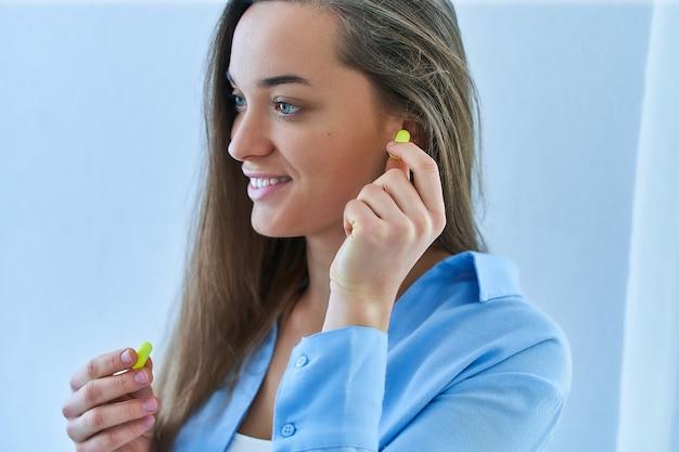 Милая счастливая молодая женщина брюнет используя беруши. защита от шума Premium Фотографии
