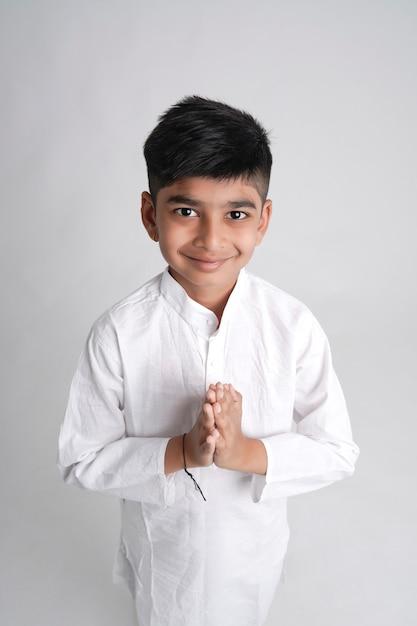 ナマステまたは白い背景の上のポーズを祈ってかわいいインドの小さな男の子 Premium写真