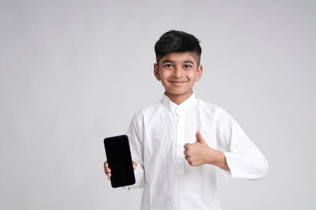 Милый индийский маленький мальчик показывает экран смартфона с копией пространства на белом фоне Premium Фотографии