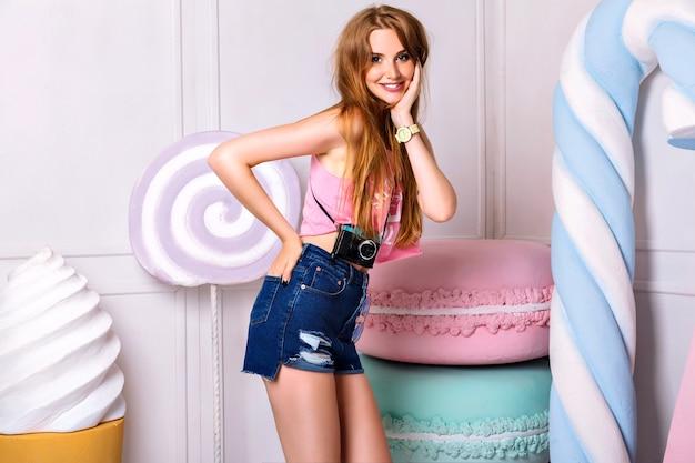 巨大なカラフルな小道具のお菓子の近くの若い美しい女性のかわいい屋内の肖像画。笑顔、顔の近くで手をつないで。ピンクの夏の一重項と青いショートパンツを着ている女の子 無料写真