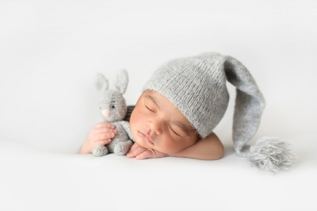 Cute infant sleeping with grey crocheted hat and with toy rabbit Free Photo