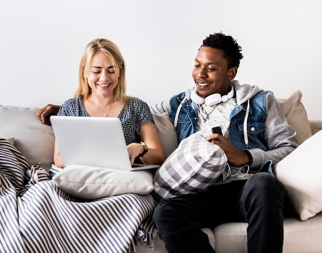 Cute interracial couple on a couch sharing laptop love, internet and music concept Premium Photo