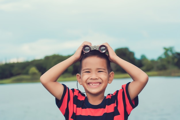 Cute kid boy standing on riverside  and with spyglass.in a happy mood. Premium Photo