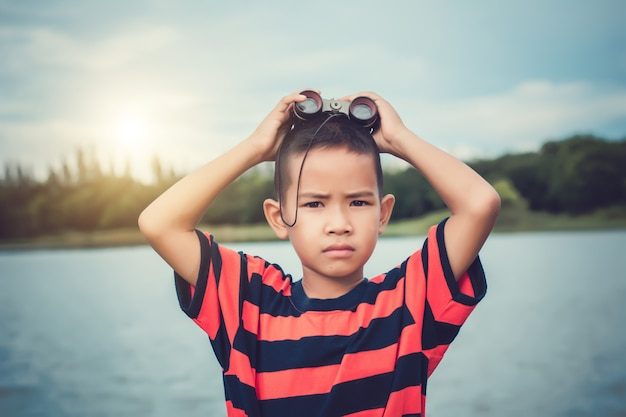 Cute kid boy standing on riverside  and with spyglass. Premium Photo