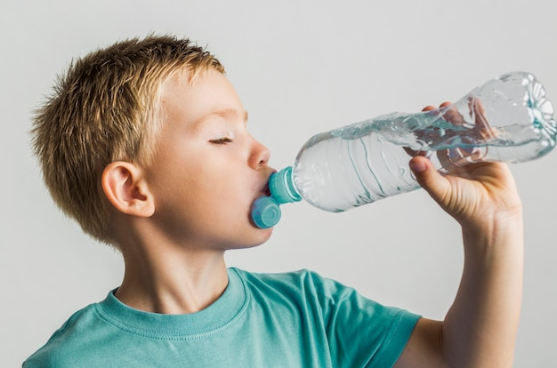 Cute kid drinking water from a plastic bottle Free Photo