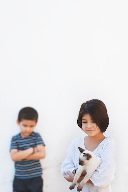 美しいシャム猫を手で押しかわいい子供女の子 Premium写真