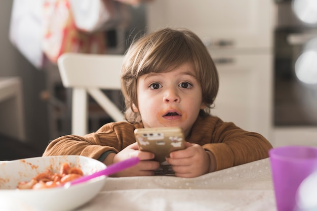 Cute kid holding phone at table Free Photo