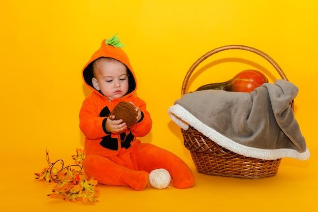 Милый ребенок в костюме тыквы на хэллоуин Premium Фотографии