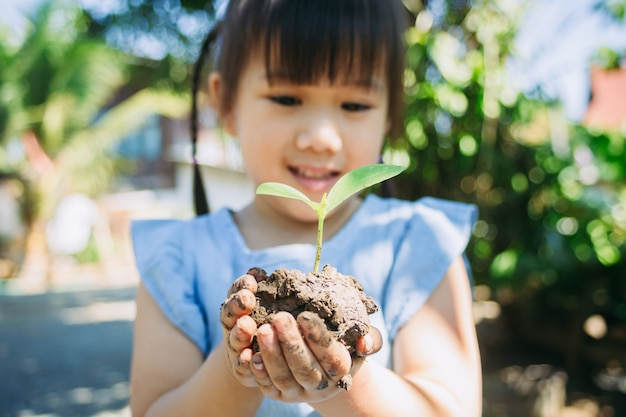 Cute kid planting a tree for help to prevent global warming or climate change and save the earth Premium Photo