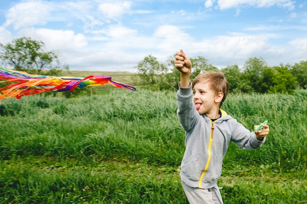 Cute kid playing with colorful kite outdoor Premium Photo