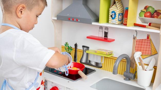 Ragazzo carino che gioca con un gioco di cucina Foto Gratuite