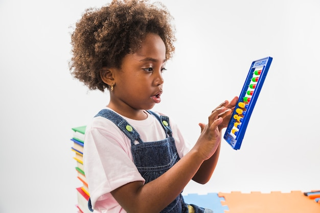 Cute kid with abacus in studio Free Photo