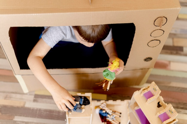 Cute kid with cardboard tv close-up Free Photo