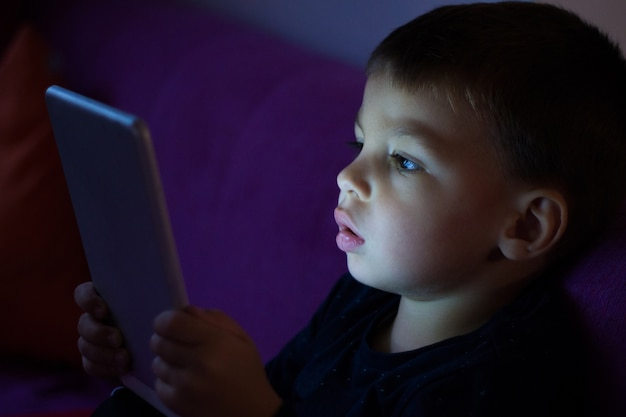 Cute kid with tablet in the dark Free Photo