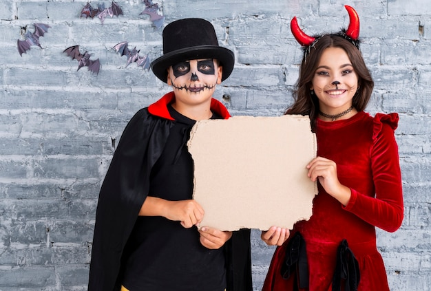 Cute kids in halloween costumes with mock-up Free Photo