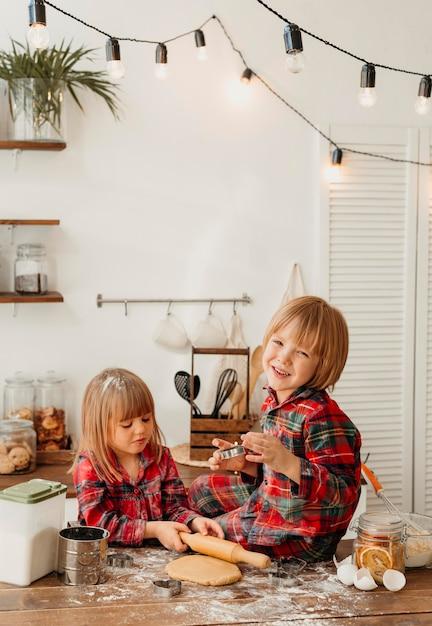 Bambini svegli che fanno i biscotti di natale insieme in cucina Foto Gratuite