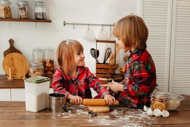 Bambini svegli che producono insieme i biscotti di natale Foto Gratuite