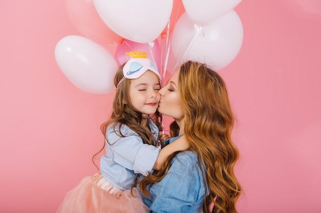 デニムシャツの若いカーリーママと誕生日パーティーでスリープマスクで素敵な娘のかわいいキス。緑豊かなスカートでキスし、母親を抱き締める長い髪の少女、面白いイベントに心から感謝 無料写真