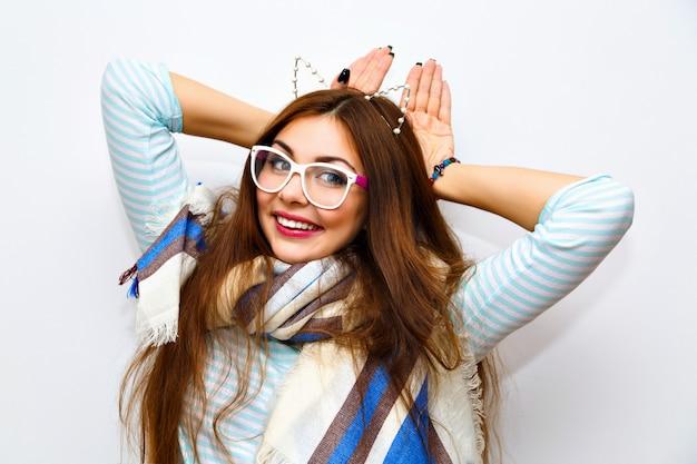 Ritratto di moda stile di vita carino di giovane donna graziosa bruna con capelli lunghi incredibili, trucco fresco e luminoso, divertirsi e gong pazzo, orario invernale, gattino imitato, orecchie da festa divertenti. Foto Gratuite