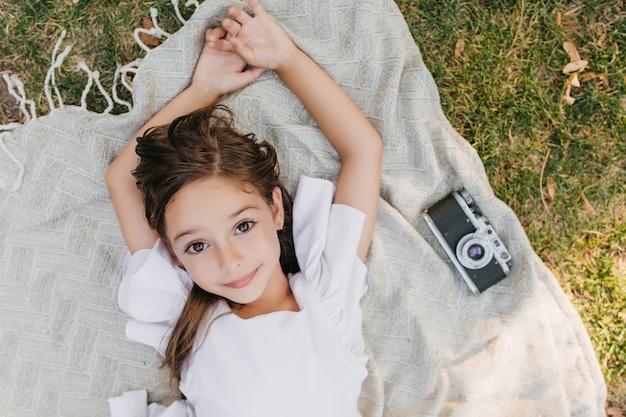 Carina ragazza leggermente abbronzata con splendidi occhi splendidi in posa sulla coperta con la macchina fotografica durante il fine settimana estivo. ritratto ambientale del bambino di sesso femminile dai capelli castani sdraiato sull'erba e sognando. Foto Gratuite