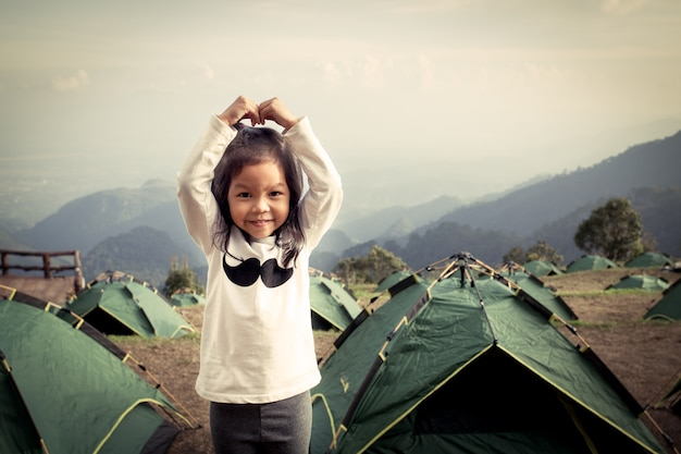 Cute litte asian girl having fun in the camp in vintage color filter Premium Photo