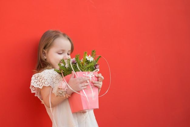 Cute litte bridesmaid holding flowers Free Photo