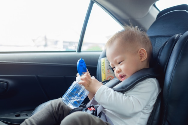 Cute little asian 18 months / 1 year old toddler baby boy child sitting in car seat holding and drinking water from cup Premium Photo