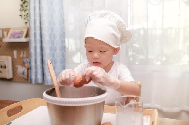 かわいい小さなアジア4歳の男の子の子供が楽しんでケーキやパンケーキの準備、自宅で卵を割る Premium写真