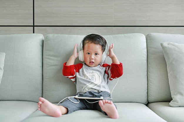 Cute little asian baby boy in headphones is using a smartphone Premium Photo