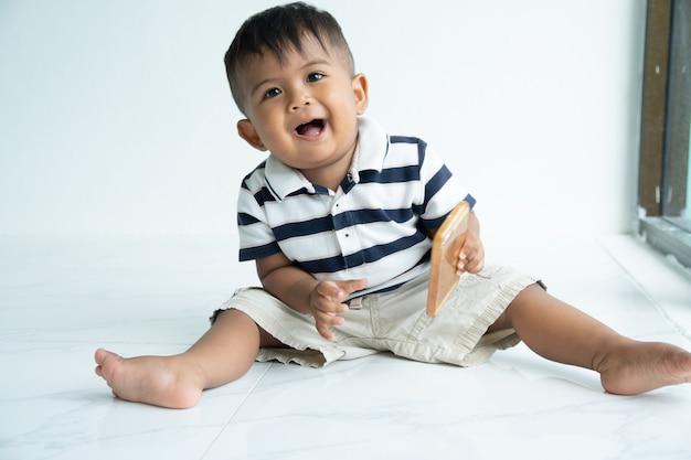 Cute little asian baby boy play smart phone Premium Photo